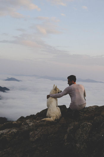 Rear view of man with dog sitting on rock against sky