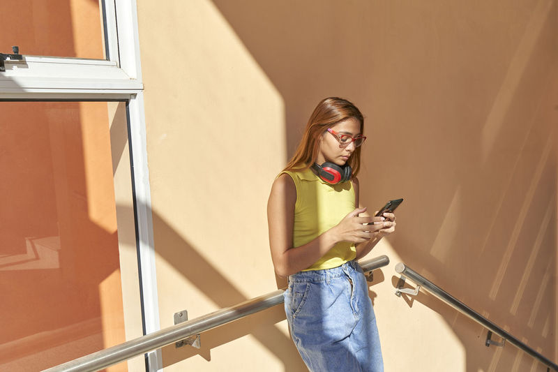 Young woman using mobile phone while standing on staircase