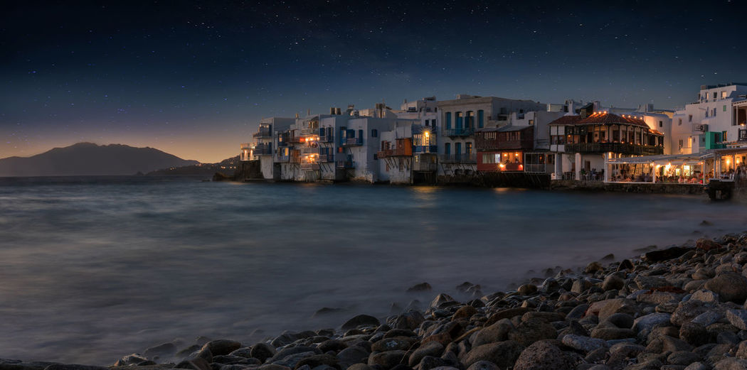 Illuminated houses by sea against sky at night