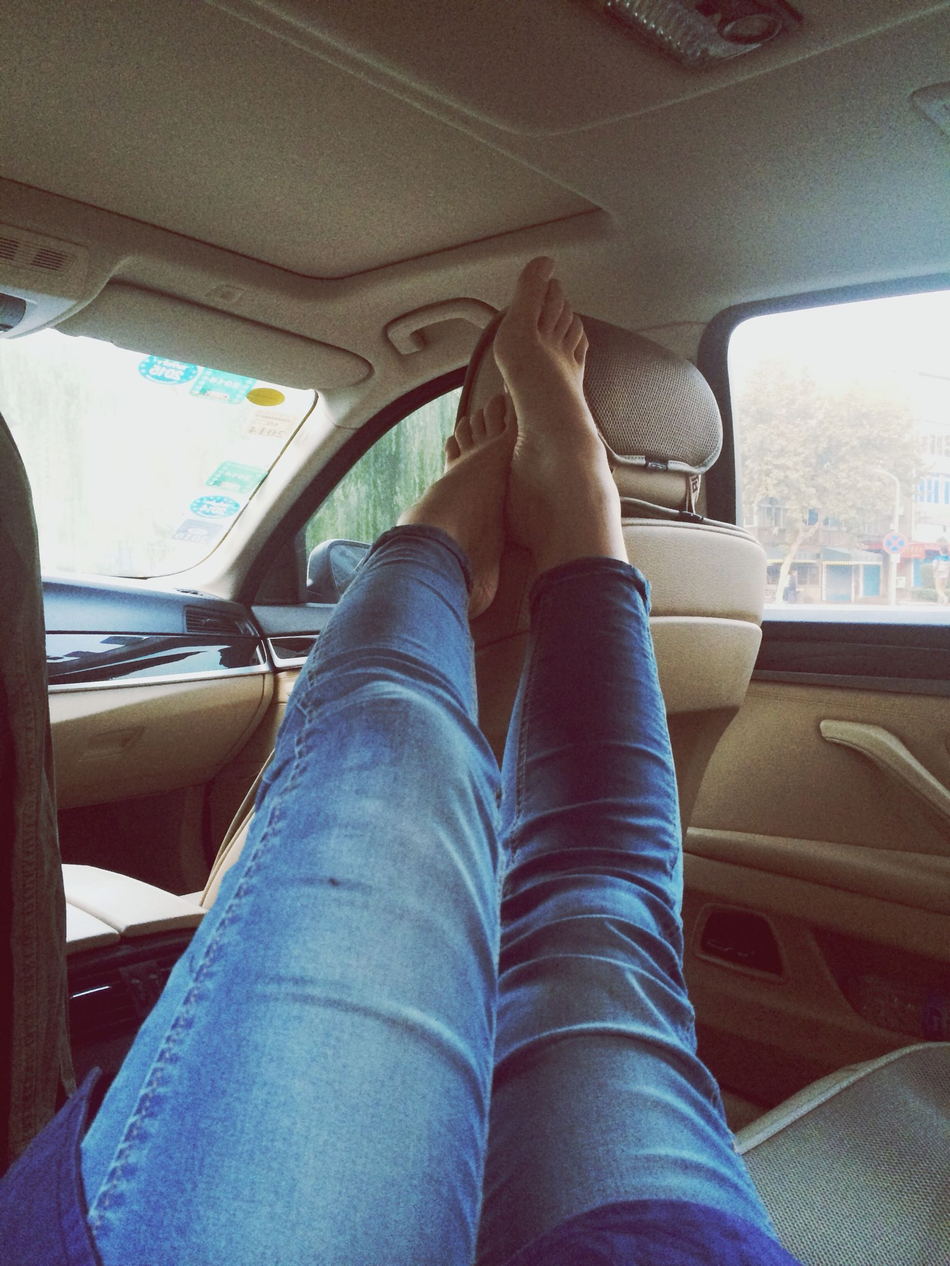 person, low section, indoors, personal perspective, sitting, lifestyles, relaxation, vehicle interior, shoe, jeans, human foot, leisure activity, legs crossed at ankle, transportation, men, casual clothing, mode of transport