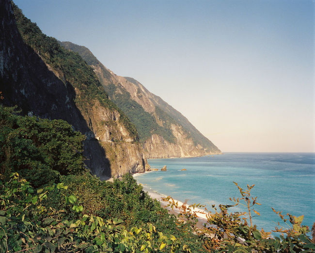 Scenic view of sea against clear sky and rocky cliffs