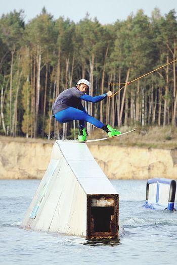 Man performing stunt on wakeboard in lake against trees