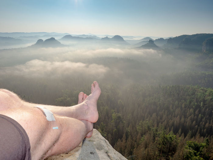 Hiker lie on edge of rock massif and relax. view over crossed legs of resting body into landscape
