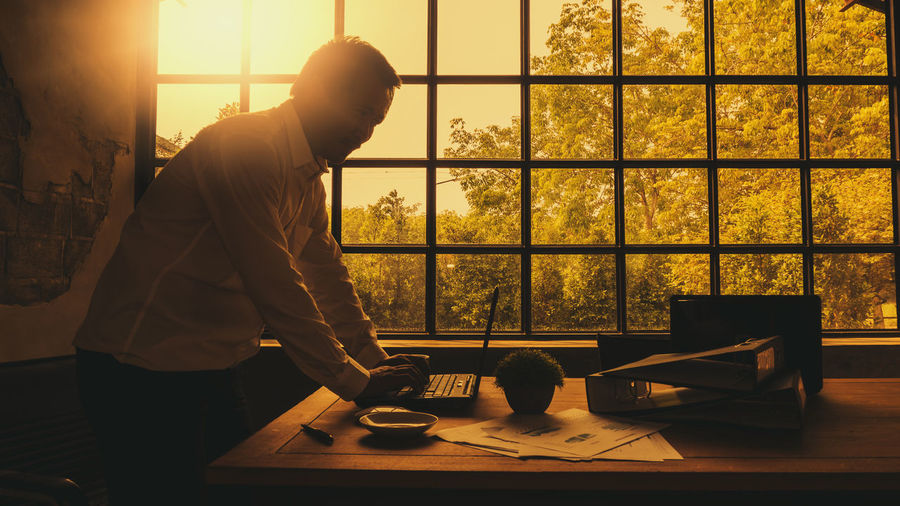 Businessmen who are diligent for business success are using laptop computers for Internet communication. Men One Person Real People Indoors  Window Standing Occupation Table Working Technology Sunlight Adult Three Quarter Length Clothing Nature Waist Up Side View Business Looking