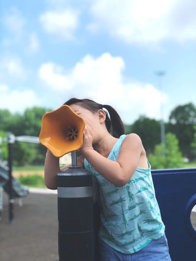 Girl shouting on megaphone at playground against sky