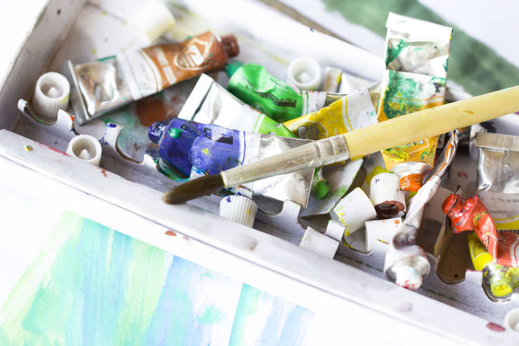High angle view of paintbrush with oil paint tubes