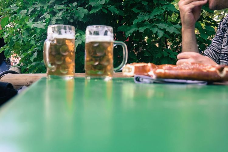 Two beers on table Adult Alcohol Beer Close-up Day Food And Drink Freshness Friendship Good Times Human Body Part Human Hand Leisure Activity One Person Outdoors People Pretzel Table