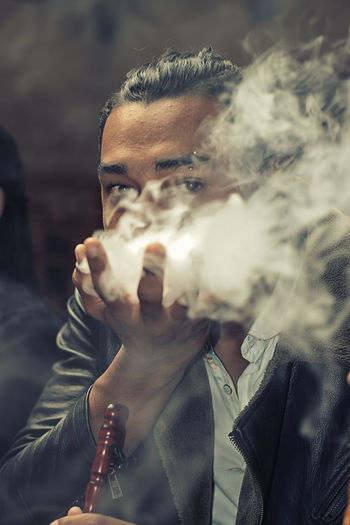 Portrait of young man playing with smoke