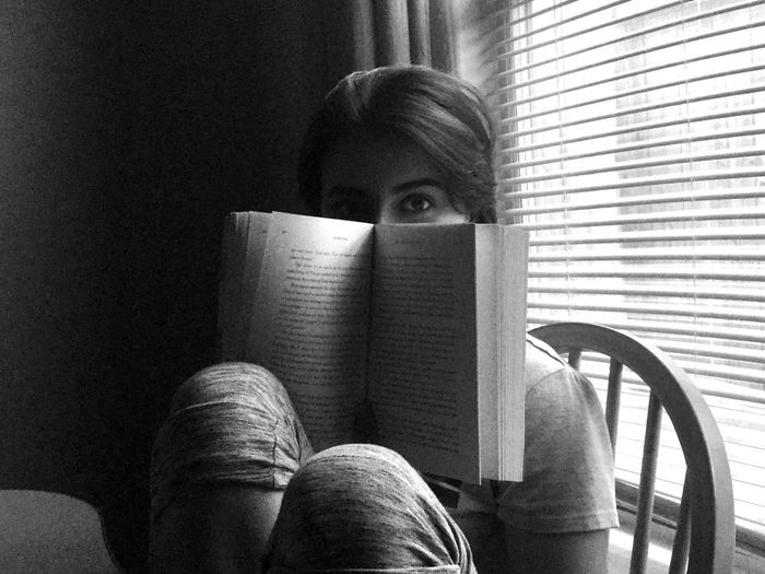 Portrait of young woman sitting with a book at home