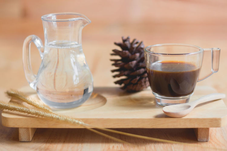 Close-up of black tea and pine cone on table
