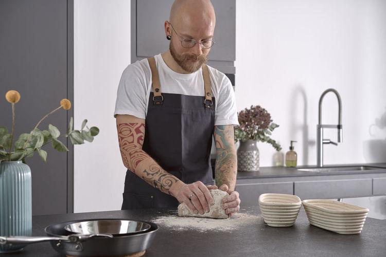 Man kneading rye sourdough on floured surface