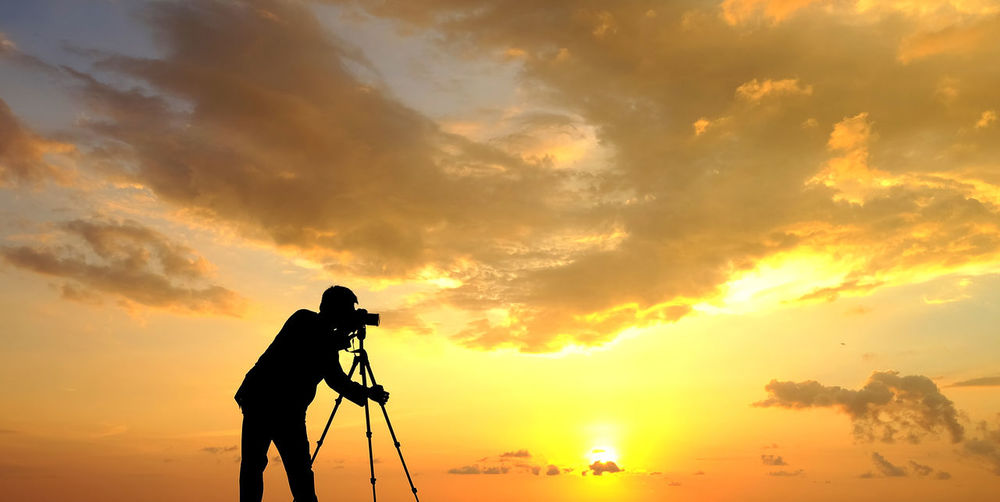 Silhouette man photographing on camera against orange sky