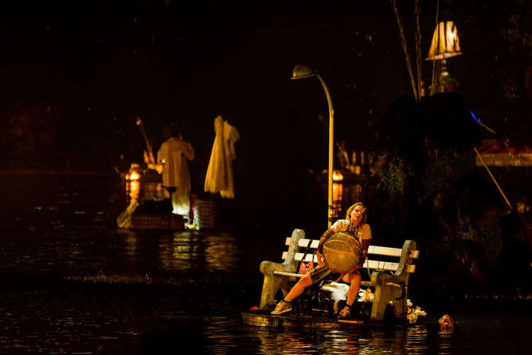 Man sitting on boat in river at night