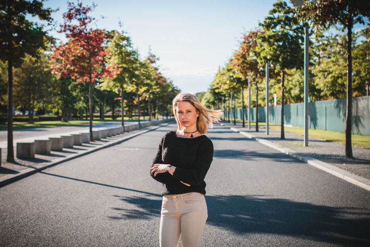 Young woman standing on road against trees