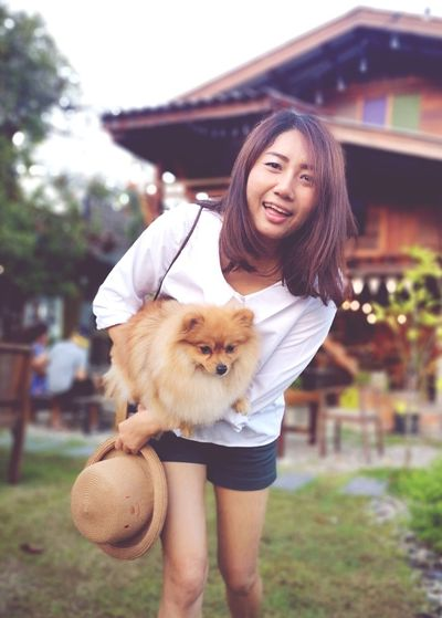 Low angle portrait of smiling woman carrying dog while standing against house