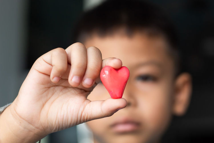 Close-up of boy holding red heart shape