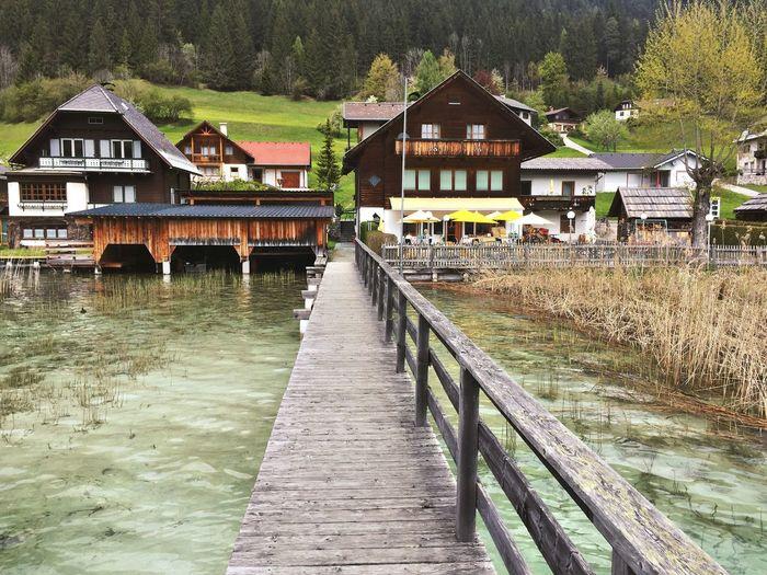 Pier amidst lake leading towards houses
