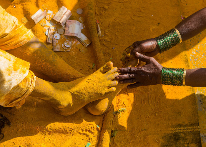 Cropped hand touching turmeric covered feet of man during tradition