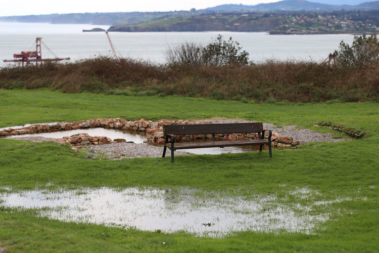 Empty bench on field by lake