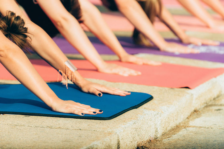 Cropped Hands Of Women Practicing Yoga Outdoors