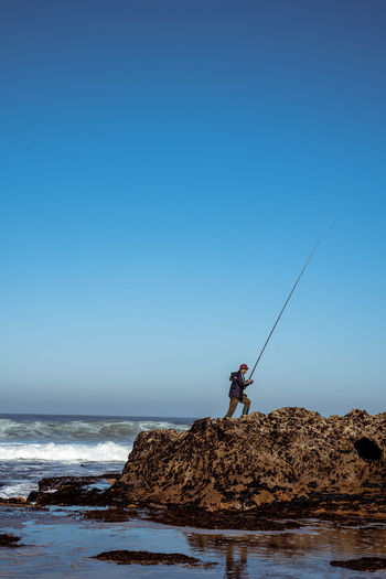 Man fishing in sea against clear sky