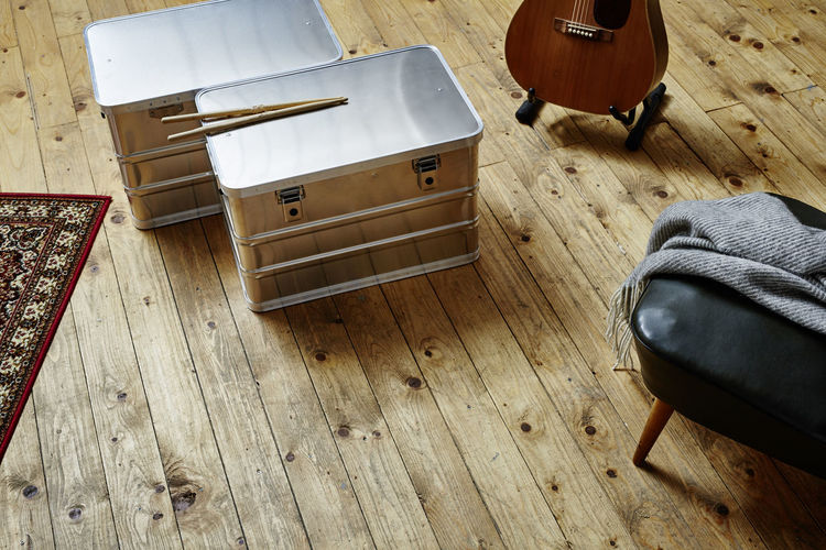 High angle view of metallic containers on hardwood floor