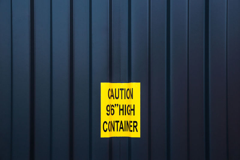 Close-up of yellow sign on cargo container