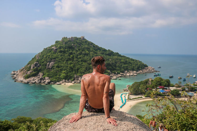 Rear view of shirtless young man looking at sea while sitting against sky