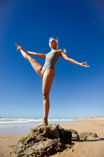 Caucasian woman practicing yoga at seashore. Young female standing on one leg while practicing the tree pose on a tranquil beach in Cadiz, Andalusia, Spain. Sky One Person Full Length Land Clear Sky Leisure Activity Human Arm Blue Beach Lifestyles Sea Nature Arms Outstretched Limb Real People Young Adult Solid Beauty In Nature Day Rock - Object Arms Raised