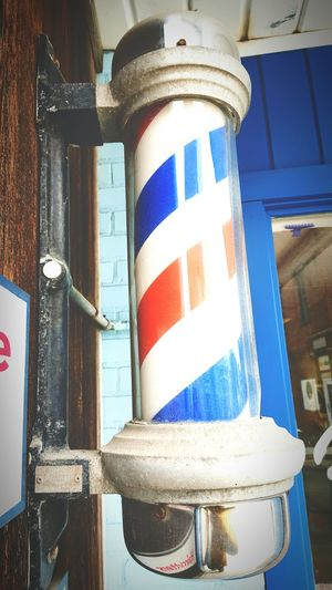 Outside the barbershop Barber Barber Pole Haircut Old-fashioned Stripes Pattern Stripes Everywhere Glass Blue And Red Red White And Blue Hairstyle Professional Outdoor Photography Street Photography Small Town Men