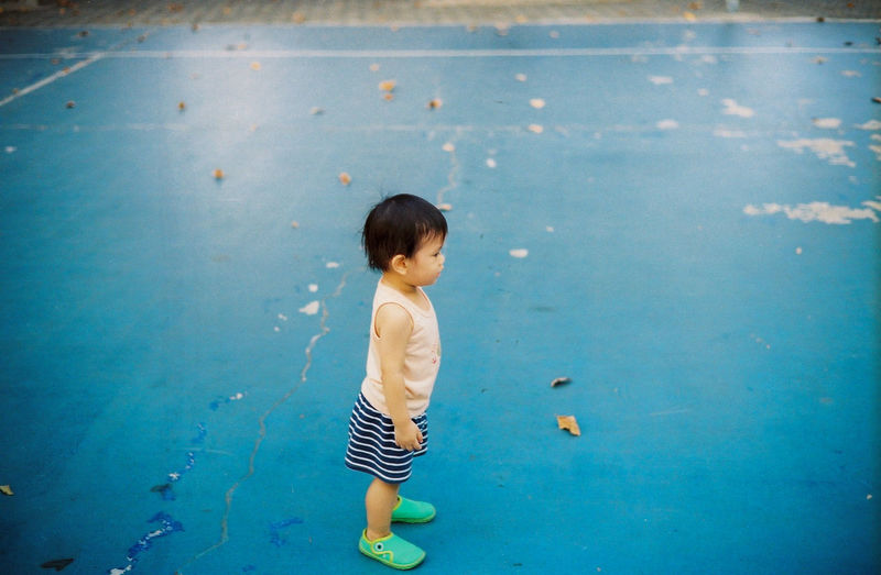 Side view of baby boy standing on old sports court