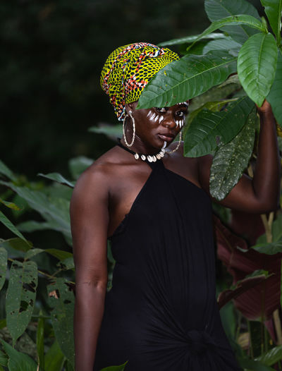 African woman standing in the jungle with tribe marks on her face and african colors as headdress