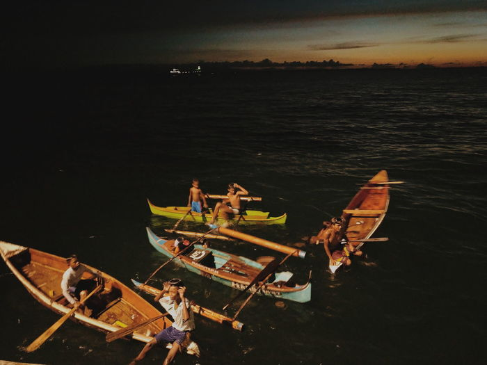 High angle view of people on sea against sky during sunset