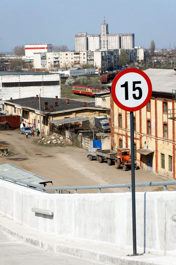 Road sign by street against buildings in city