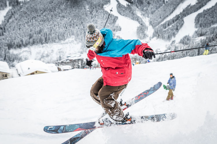 Cold Temperature Snow Winter Sport Winter Sport Mountain Leisure Activity Real People Clothing Day Motion Full Length Lifestyles Nature Extreme Sports White Color Skiing Two People People Warm Clothing Outdoors Ski-wear