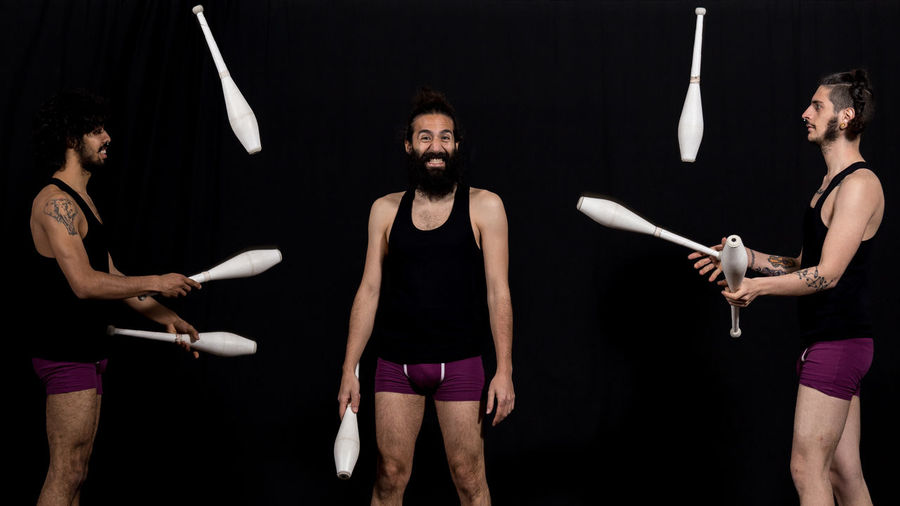 Circus jugglers during their devilsticks performance Adult Circus Fun Man Show Skill  Teamwork Acrobat Background Black Coordination Different Entertainment Juggler Juggling Lifestyles Men People People Photography Performance person Real People Stage - Performance Space Team Three People