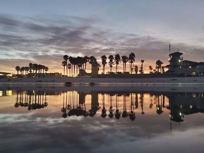 Reflection of buildings in ocean at sunset