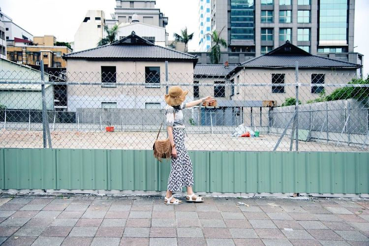 Woman Walking By Fence