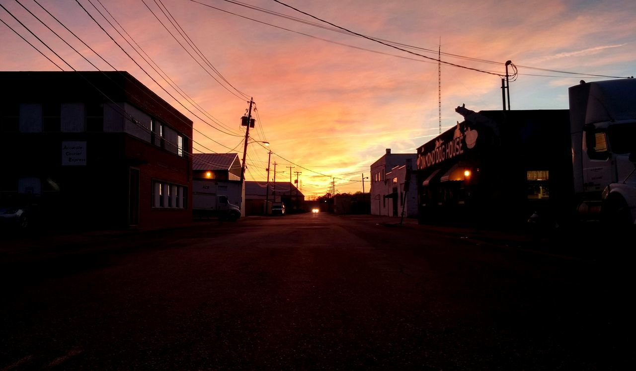 sunset, architecture, built structure, sky, building exterior, cable, street, road, the way forward, city, power line, transportation, cloud - sky, dusk, electricity pylon, outdoors, no people, silhouette, nature, telephone line, day