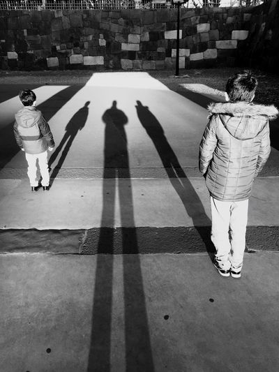 Rear view of boys standing on street