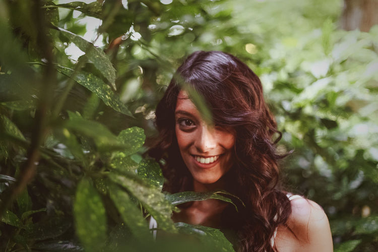 Portrait Of Smiling Young Woman Standing Amidst Plants In Park