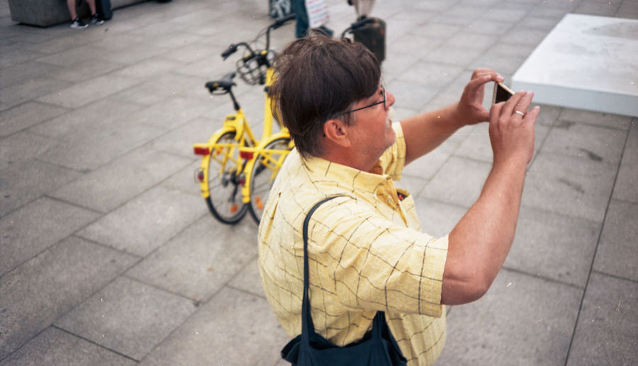 High angle view of man holding bicycle on street
