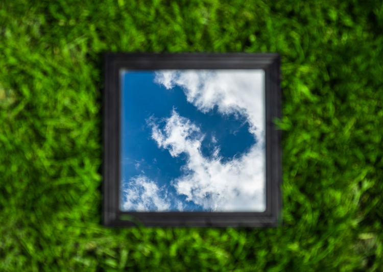 Low angle view of glass window against blue sky