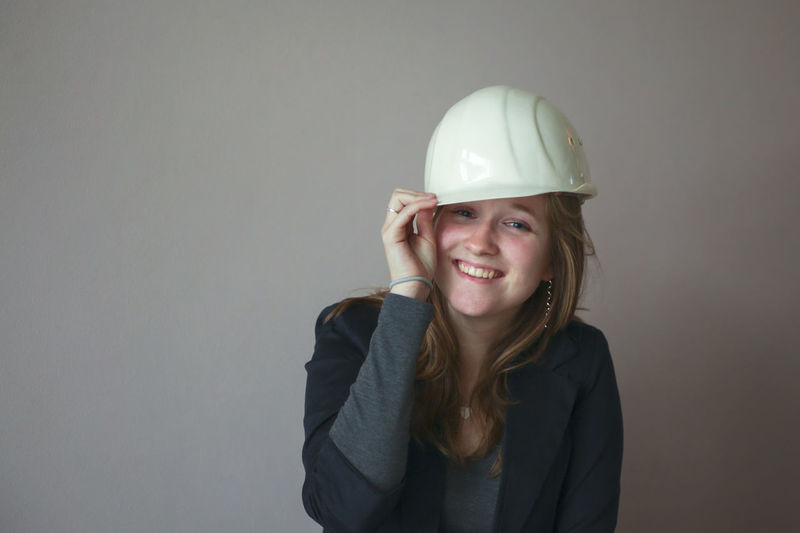 Young woman with hard hat laughing Architecture Attractive Built Structure Business Casual Clothing Confidence  Engineer Female Front View Fun Girl Hard Hat Headshot Helmet Industrial Laughing Laughing Out Loud Lifestyles Portrait Professional Safety Helmet Smiling Woman Work Young