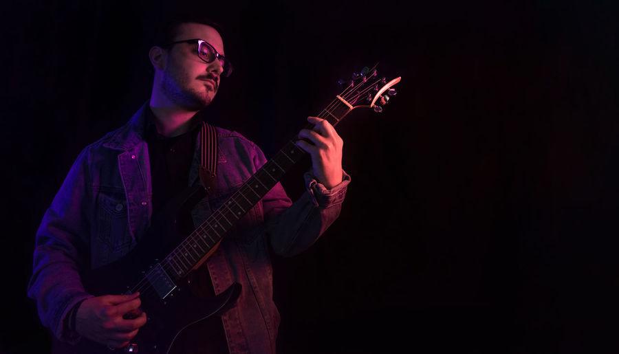 Young man playing guitar at night