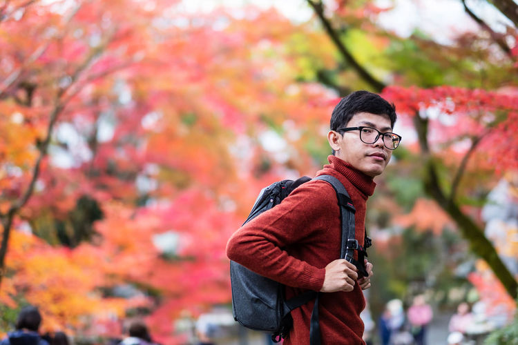 Portrait of young man standing against autumn leaves