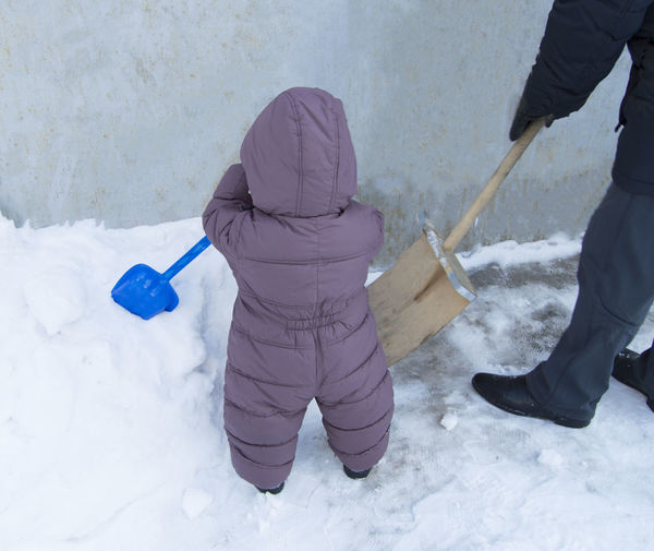 High angle view of child holding snow on field