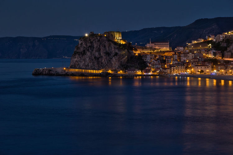 Illuminated buildings by sea against sky at night