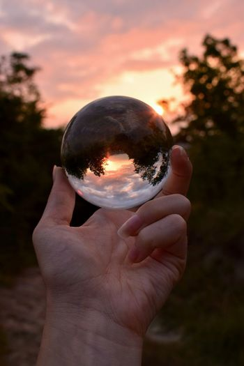 Cropped man holding crystal ball against cloudy sky during sunset
