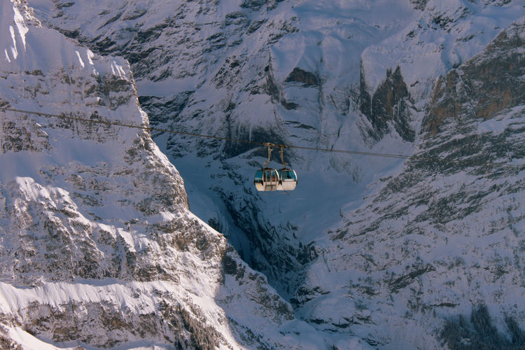 Overhead cable car hanging by snowcapped mountains